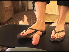 Blonde in flip flops is standing on his dick through a cock